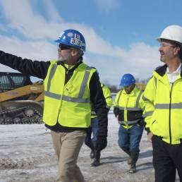 Two Industrial workers walking near industrial site
