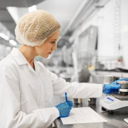 Woman in lab weighing an item